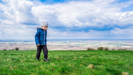 stay in the green: young handsome boy walking on green grass and enjoying his stay on fresh air