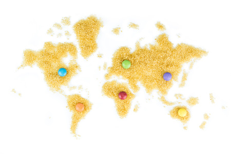smarties: map of the world made of cane sugar on white background with multicoloured smarties laying on the map