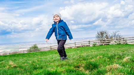 stay in green: young handsome boy walking on green grass and enjoying his stay on fresh air