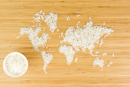 geography map: map of the world made of white rice on bamboo wood background with white bowl full of rice