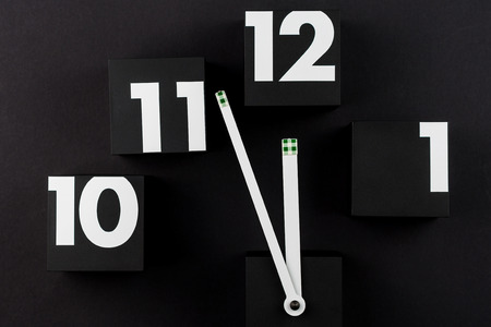 five to twelve: five minutes before twelve with black cubes as digits of big clock on black background
