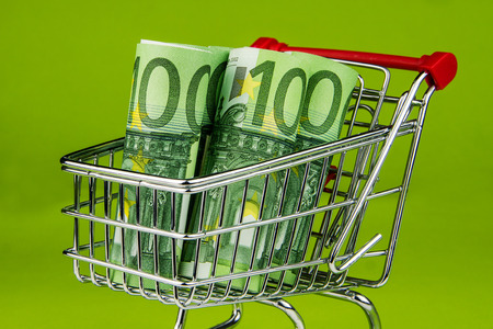 one hundred euro banknote: five one hundred euro banknote rolls laying in shopping cart on green background