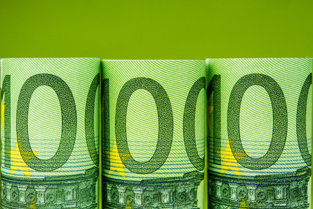 one hundred euro banknote: five one hundred euro banknote rolls in one row on green background Stock Photo