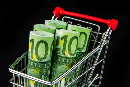 one hundred euro banknote: five one hundred euro banknote rolls laying in shopping cart on black background