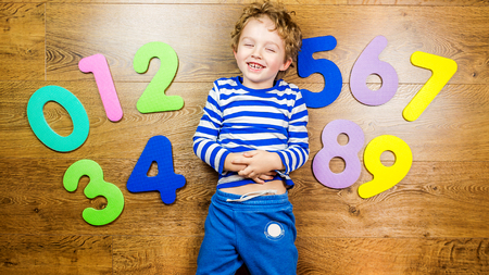 young boy demonstrating his collection of numbers with happy and smiling face while laying on brown wooden floor Stock Photo