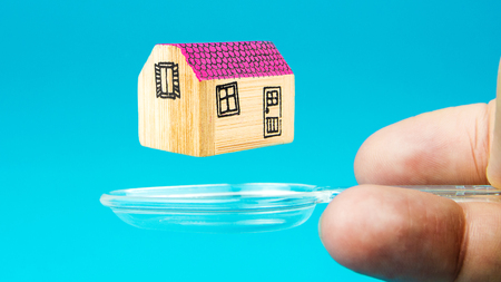 levitation: a man is holding translucent spoone with levitation of a miniature of wooden house