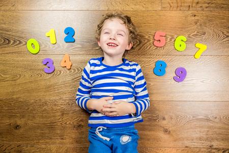 jonge jongen tonen zijn verzameling van nummers met gelukkig en lachende gezicht terwijl tot op bruine houten vloer Stockfoto