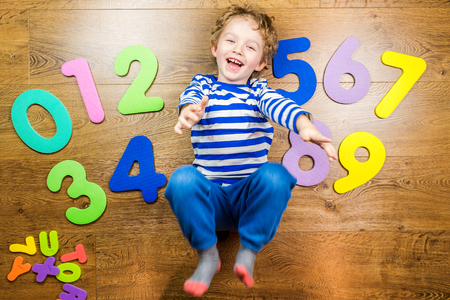 little boys: young boy demonstrating his collection of numbers with happy and smiling face while laying on brown wooden floor Stock Photo