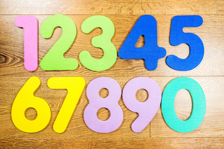 laying on back: playing with multicolored plastic numbers on wooden background Stock Photo