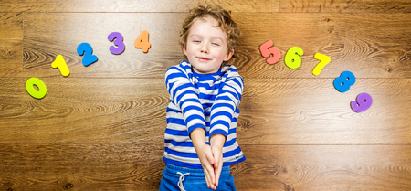 unfold: young boy demonstrating his collection of numbers with happy and smiling face while laying on brown wooden floor Stock Photo