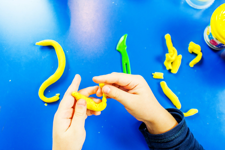 modeling clay: young boy is playing with plasticine on blue table with many colors of modeling clay