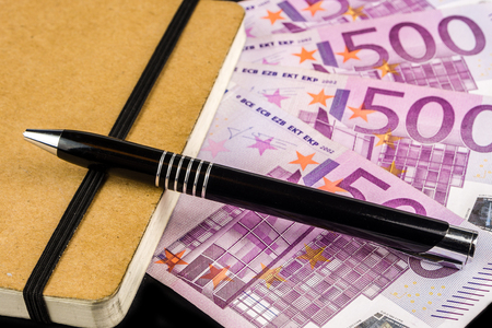 old diary: old diary with a pen and big euro banknotes on black background Stock Photo