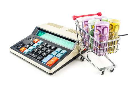 inflation basket: silver shopping trolley full of euros with old styled calculator on white background