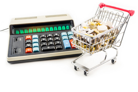 misuse: shopping cart full of vitamin supplements on white background with retro calculator in the back