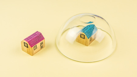 protect: how to protect your house, one miniature wooden house protected and the other one not protected with a glass jar upside down on yellow background