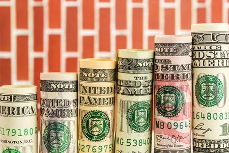 salarios: el aumento de escalones de todos los rollos de billetes de dólar americano en una fila en el fondo de la pared roja
