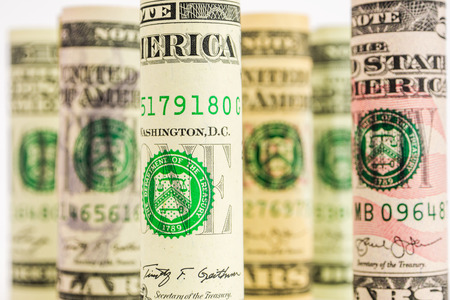 american dollar banknote rolls in all denominations on white background with one dollar banknote focus and others defocused