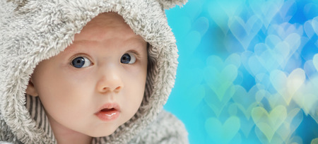 pyjama: closeup of beautiful happy baby with blue eyes in grey bear like clothing on blue heart shaped background
