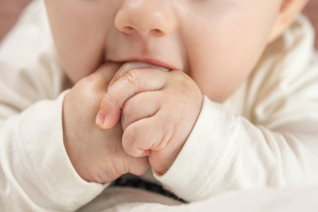 pyjama: closeup of beautiful happy baby biting on his hands on red brick background