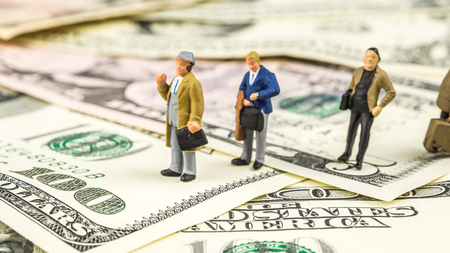 business concept, closeup of miniature figurine of people waiting in line for money  wages