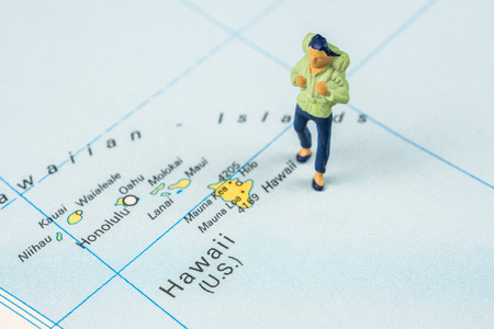 closeup of miniature figurine of young traveller standing on big map next to Hawaii islands Stock Photo