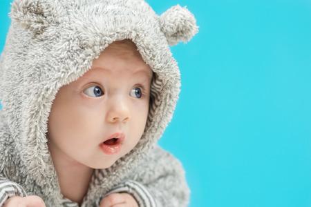 pyjama: closeup of beautiful amazed happy baby with blue eyes in grey bear like clothing on blue background Stock Photo