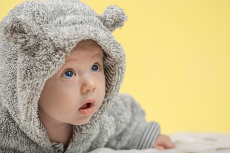 pyjama: closeup of beautiful happy baby with blue eyes in grey bear like clothing on yellow background Stock Photo