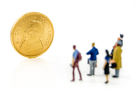 people looking at golden kruegerrand coin on white background
