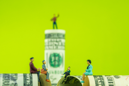 miniature figurines sitting on the edge of 100 dollar banknote with a defocused man standing on dollar bill at the back on green background