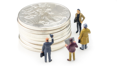 group of businessmen miniature figurines standing in front of silver american eagle coins on white background Stock Photo