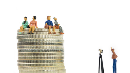 group of people miniature figurines sitting on silver american eagle coins with a photograph taking a picture of them on white background