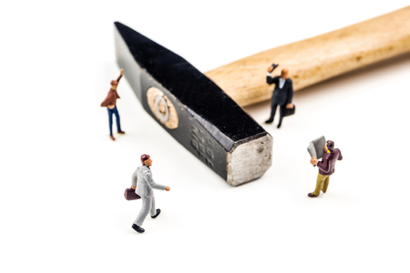 closeup of miniature figurines of businessmen having a meeting with big hammer in the center on white background