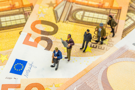 business concept, closeup of miniature figurine of businessmen standing in line on new 50 euro banknotes about finance, business changes and problems