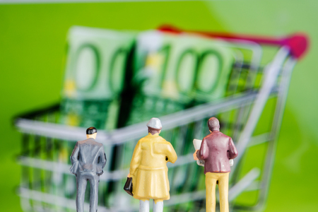 closeup of miniature figurines of businessmen standing in front of big defocused screen with 100 euro banknotes in shopping rolley