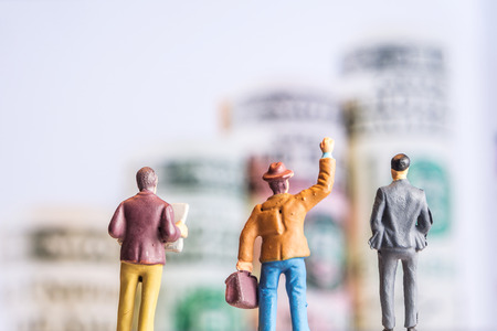 closeup of miniature figurines of businessmen standing in front of big defocused screen with american dollar banknotes forming an uprising graph Stock Photo