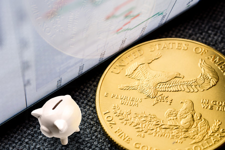 closeup of golden american eagle coin with a chart reflection on close digital device with green and red bars and miniature ceramic white pig for saving money Stock Photo