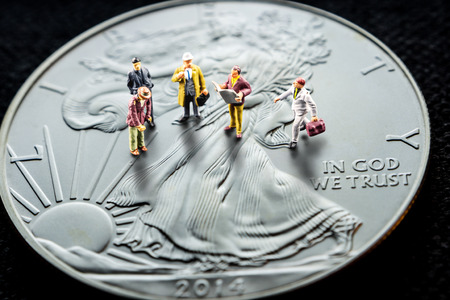 closeup of silver american eagle coin and miniature business men figurines having a meeting