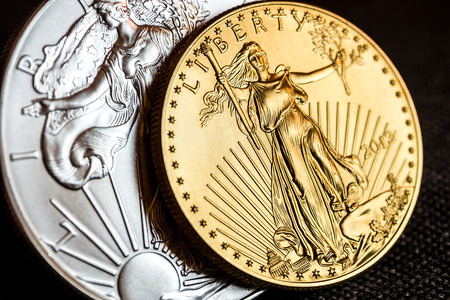 silver coins: closeup of silver eagle and golden american eagle one ounce coins on black background