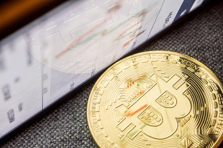 closeup of golden bitcoin coin with a chart reflection on its surface with green and red bars Stock Photo