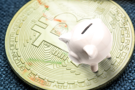 closeup of golden bitcoin coin with a chart reflection on its surface with green and red bars and white ceramic pig laying on a coin Stock Photo