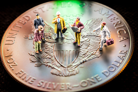 closeup of silver american eagle coin with a reflection of close digital device and miniature business men figurines having a meeting Stock Photo