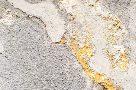 closeup of dirty white concrete wall with facade detail and many irregularities
