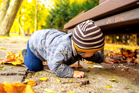view of young boy in an autumn park with a lot of leaf spreaded all around searching something under a park bank