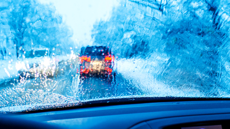 closeup of front car window with raindrops and blurred heavy traffic during rush hour in winter with blue colour shade