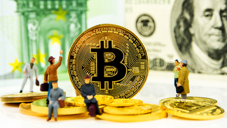 closeup of golden bitcoin coin on dollar banknote background with many golden coins at bottom and miniature figurines standing around Stock Photo