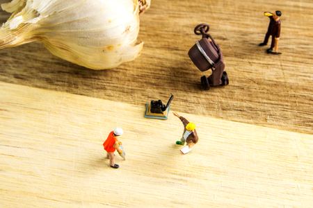miniature figurines working hard together in order to make garlic best possible