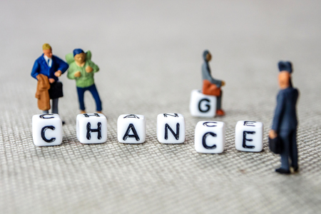 """Changing white cubes with word """"change"""" to """"chance"""", personal development and career growth or change yourself concept, grey background with miniature figurines watching at it"""