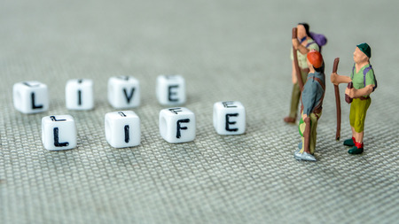personal development and growth or just live life concept, grey background with miniature figurines watching at it Stock Photo