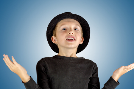 closeup of young boy in black shirt and black hat with merry smiling and litlle bit surprised expression