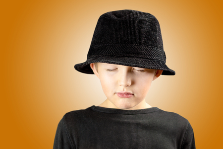 closeup of young boy in black shirt and black hat with very calm, meditating and focused expression of his face and body gesture with free copy space for the text and golden background Stock Photo